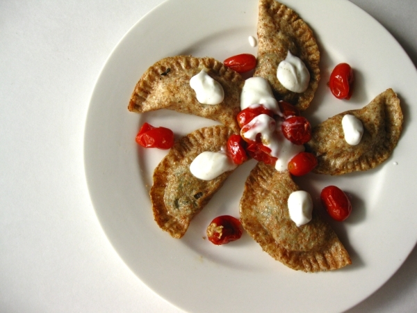 Spinch and eggplant perogies with grape tomatoes and yogurt sauce