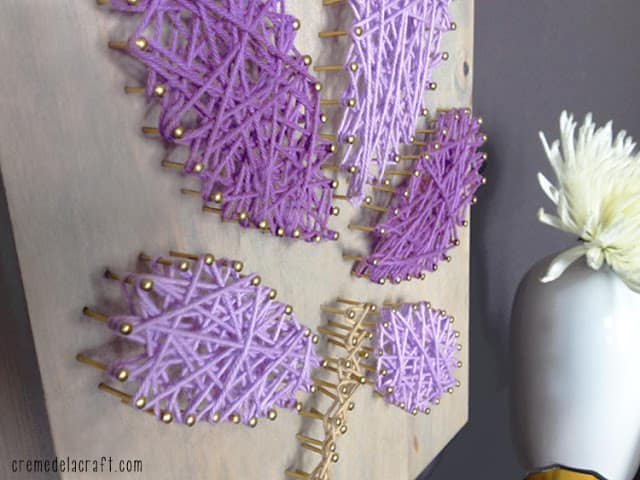 Purple flower yarn and nails wall art