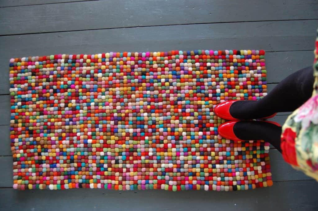 Warm, colourful pom pom rug