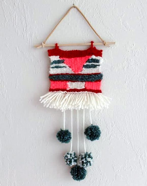 Woven wall hanger with pom poms
