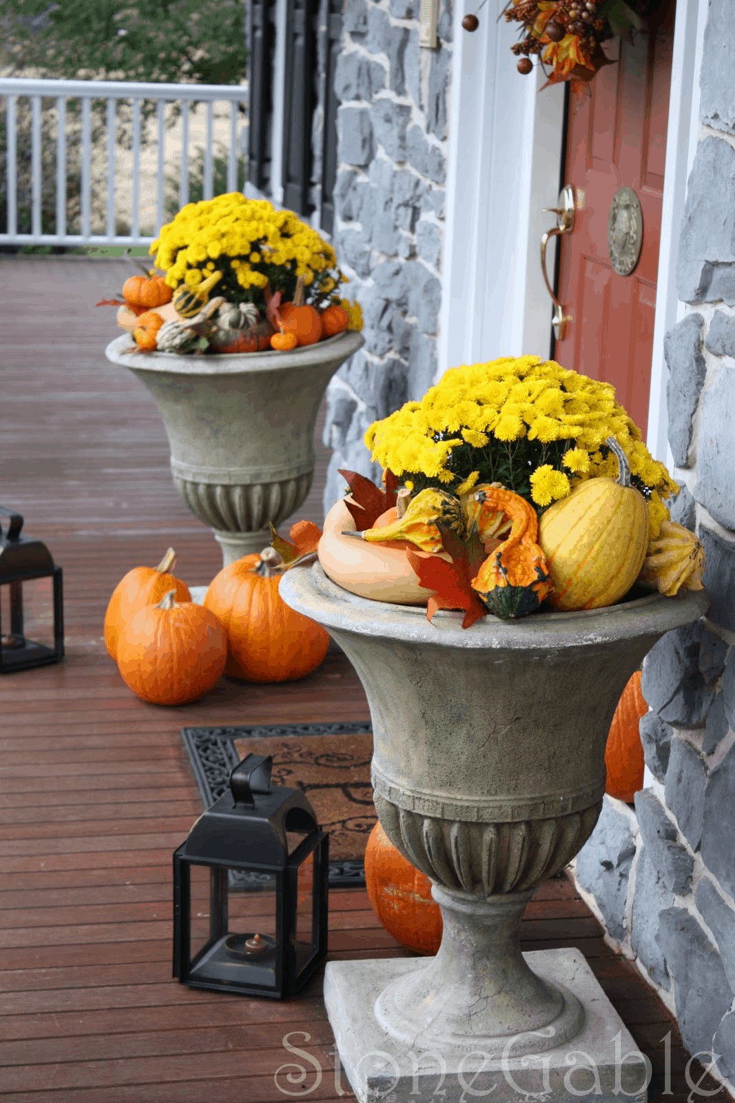 Stone pedestal planters filled with fall coloured flowers and gourds