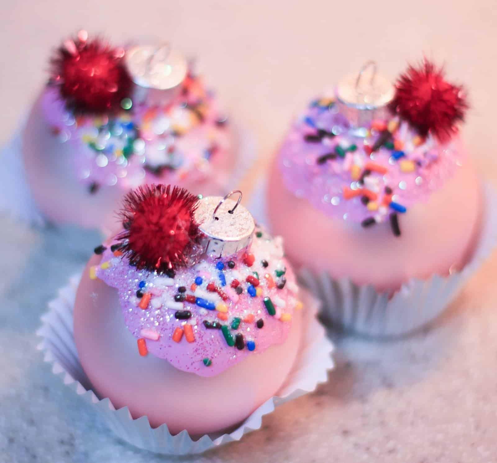 Pom pom and sprinkle Christmas ornament cupcakes 15 Delicious Christmas Cupcake Ideas and Recipes