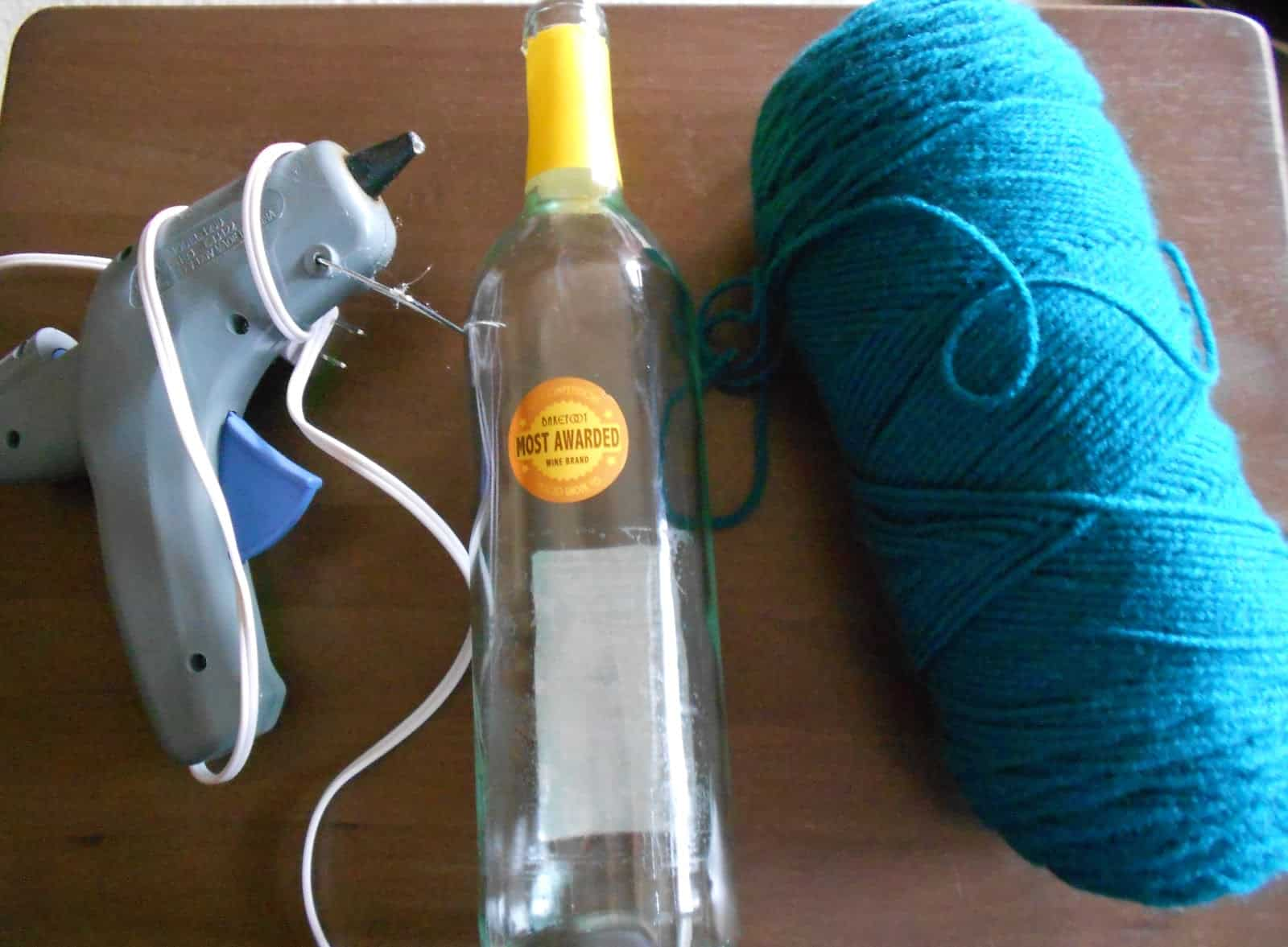 Painted wine bottle, yarn, and hot glue decor