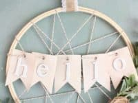 22Hello22 bunting farmhouse wreath 200x150 15 Awesome Projects Made Using Embroidery Hoops