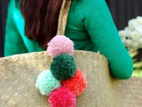 DIY layered pom pom tote tassel 200x150 Unleash Cuteness: 15 Fuzzy DIY Projects Made With Pom Poms