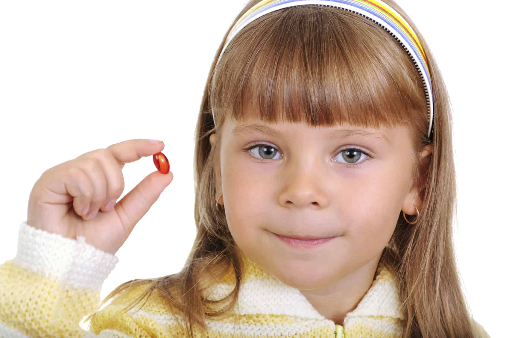 The smiling girl holds a medicinal capsule in a hand