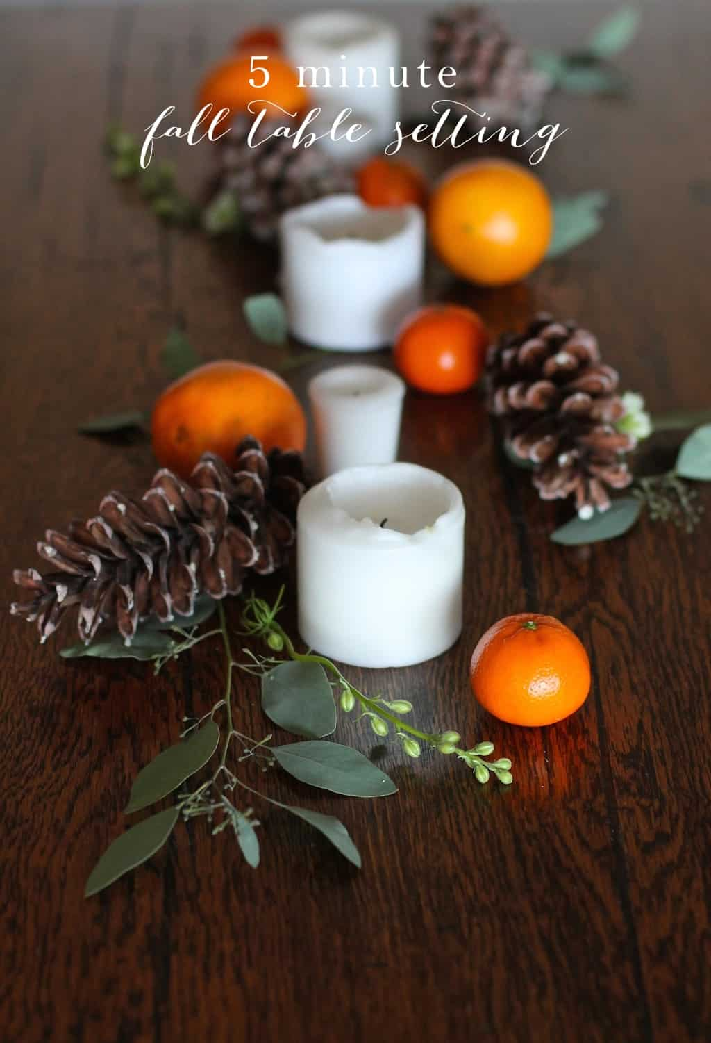 5-minute table setting with candles, oranges, and pine cones
