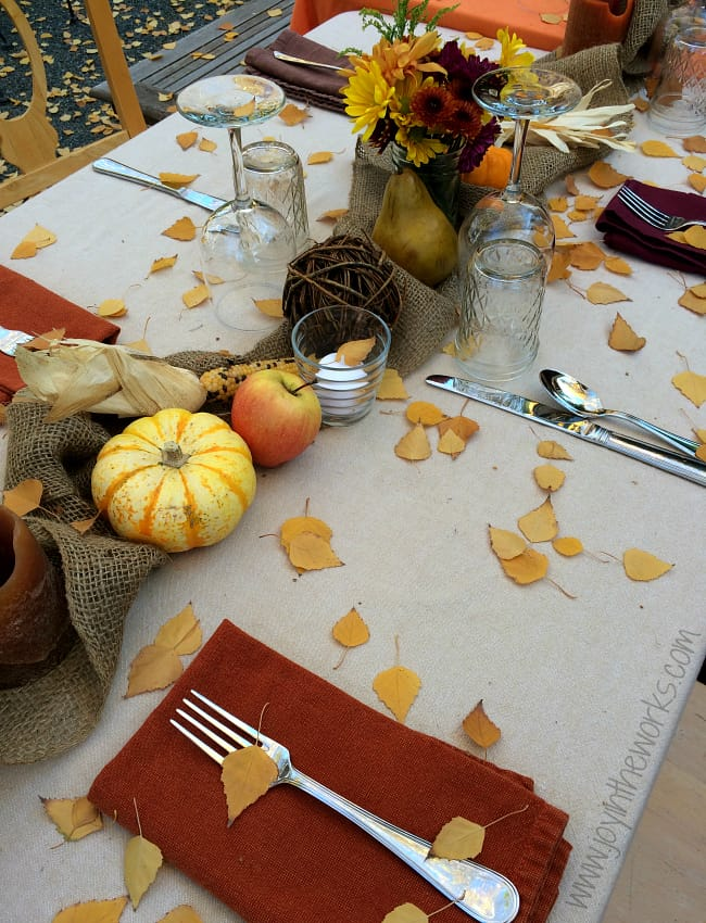 Outdoor gathered burlap and scattered leaves tablescape